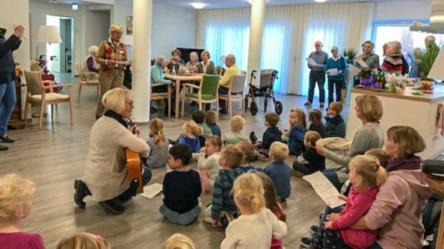 23 Jungen udn Mädchen aus der Kita St. Lambertus sorgten mit ihren Liedern und Tänzen in der Senioren-WG für Stimmung. Foto: SMMP/Bettina Czischke